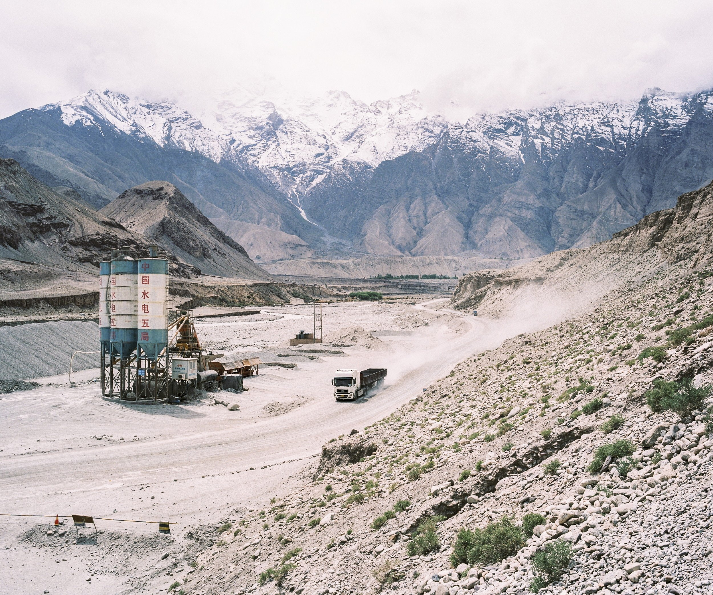 "May 2016. Xinjiang province, China. View of road G314 in China, aka the Karakoram highway, the road linking the western Chinese province of Xinjiang with Pakistan through the Pamir mountains. On the right is the Baishahu lake. A new road should be finished by 2017 to increase trade between the two countries.  Xinjiang is the westernmost province in all China, located at the border of Central Asian countries, Russia and Mongolia. More than twice the size of France, it has only 22 million inhabitants, a majority of which are the indigenous Uighurs, a sunni-muslim Turkic ethnic group which has lived in the region for centuries. Tensions have nonetheless arisen in the last decade as a consequence of the en-masse migration of Han Chinese settlers and confessional persecution by the strongly secular governmental authorities.  Borrowing from romanticized notions of the American frontier, synonymous with ideals of exploration and expansion, photographer Patrick Wack captures a visual narrative of China's westernmost region—Xinjiang. Whereas the American West conjures images of cowboys and pioneers, of manifest destiny and individualistic freedom, the Chinese West has not yet been so defined. It is a place of pluralities—of haunting, expansive landscapes, of rough mountains and vivid lakes, of new construction and oil fields, of abandoned structures in decaying towns, of devout faith and calls to prayer, of silence and maligned minorities, of opportunity and uncertain futures. It is a land of shifting identity. In essence, Xinjiang is the new frontier to be conquered and pondered. Literally translating to ""new frontier"" in Chinese, Xinjiang is a land apart, and has been so for centuries. More than twice the land area of France with a population less than the city of Shanghai, the Chinese province of Xinjiang once connected China to Central Asia and Europe as the first leg of the ancient Silk Road. Yet it remains physically, culturally, and politically distinct, an otherness within modern China. Its infinite sense of space; its flowing Arabic scripts and mosque-filled cityscapes; its designation as an autonomous region; and simmering beneath, its uneasy relationship with the encroaching, imposing, surveilling East. For China's ethnic Han majority, Xinjiang is once again the new frontier, to be awakened for Beijing's new Silk Road—China's own manifest destiny—with the promise of prosperity in its plentiful oil fields. For Patrick Wack, Out West is as a much a story of the region as it is his own, as much a documentation of a contemporary and historical place as it is an emotional journey of what it means to strive, and for what. There exists an inherent fascination in the region—as both key and foil to the new China—and a siren's call to its vast limitlessness that instinctively incites introspection and desire. Showcasing a romanticism of the frontier, Out West presents Xinjiang via the lens of its present day, in photography that speaks of the surrealistic tranquility—and disquiet—of the unknown. Out West offers an experience of Xinjiang that highlights its estrangement from contemporary perceptions of the new China, accentuating undercurrents of tension and the mystique it has cultivated—whether in their minds or ours. At its core, Out West is a question of perspective: What is the West but the East to another?"