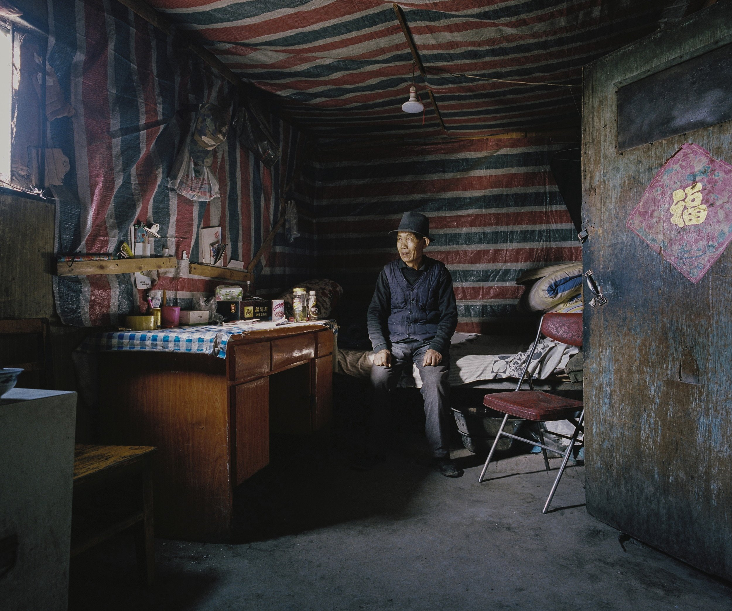 "December 2016. Xinjiang province, China. Old Han Chinese man photographed in the bedroom of his house. He is the guardian of a mine in the Taklmakan desert in the western Chinese province of Xinjiang. Xinjiang is the westernmost province in all China, located at the border of Central Asian countries, Russia and Mongolia. More than twice the size of France, it has only 22 million inhabitants, a majority of which are the indigenous Uighurs, a sunni-muslim Turkic ethnic group which has lived in the region for centuries. Tensions have nonetheless arisen in the last decade as a consequence of the en-masse migration of Han Chinese settlers and confessional persecution by the strongly secular governmental authorities.  Borrowing from romanticized notions of the American frontier, synonymous with ideals of exploration and expansion, photographer Patrick Wack captures a visual narrative of China's westernmost region—Xinjiang. Whereas the American West conjures images of cowboys and pioneers, of manifest destiny and individualistic freedom, the Chinese West has not yet been so defined. It is a place of pluralities—of haunting, expansive landscapes, of rough mountains and vivid lakes, of new construction and oil fields, of abandoned structures in decaying towns, of devout faith and calls to prayer, of silence and maligned minorities, of opportunity and uncertain futures. It is a land of shifting identity. In essence, Xinjiang is the new frontier to be conquered and pondered. Literally translating to ""new frontier"" in Chinese, Xinjiang is a land apart, and has been so for centuries. More than twice the land area of France with a population less than the city of Shanghai, the Chinese province of Xinjiang once connected China to Central Asia and Europe as the first leg of the ancient Silk Road. Yet it remains physically, culturally, and politically distinct, an otherness within modern China. Its infinite sense of space; its flowing Arabic scripts and mosque-filled cityscapes; its designation as an autonomous region; and simmering beneath, its uneasy relationship with the encroaching, imposing, surveilling East. For China's ethnic Han majority, Xinjiang is once again the new frontier, to be awakened for Beijing's new Silk Road—China's own manifest destiny—with the promise of prosperity in its plentiful oil fields. For Patrick Wack, Out West is as a much a story of the region as it is his own, as much a documentation of a contemporary and historical place as it is an emotional journey of what it means to strive, and for what. There exists an inherent fascination in the region—as both key and foil to the new China—and a siren's call to its vast limitlessness that instinctively incites introspection and desire. Showcasing a romanticism of the frontier, Out West presents Xinjiang via the lens of its present day, in photography that speaks of the surrealistic tranquility—and disquiet—of the unknown. Out West offers an experience of Xinjiang that highlights its estrangement from contemporary perceptions of the new China, accentuating undercurrents of tension and the mystique it has cultivated—whether in their minds or ours. At its core, Out West is a question of perspective: What is the West but the East to another?"
