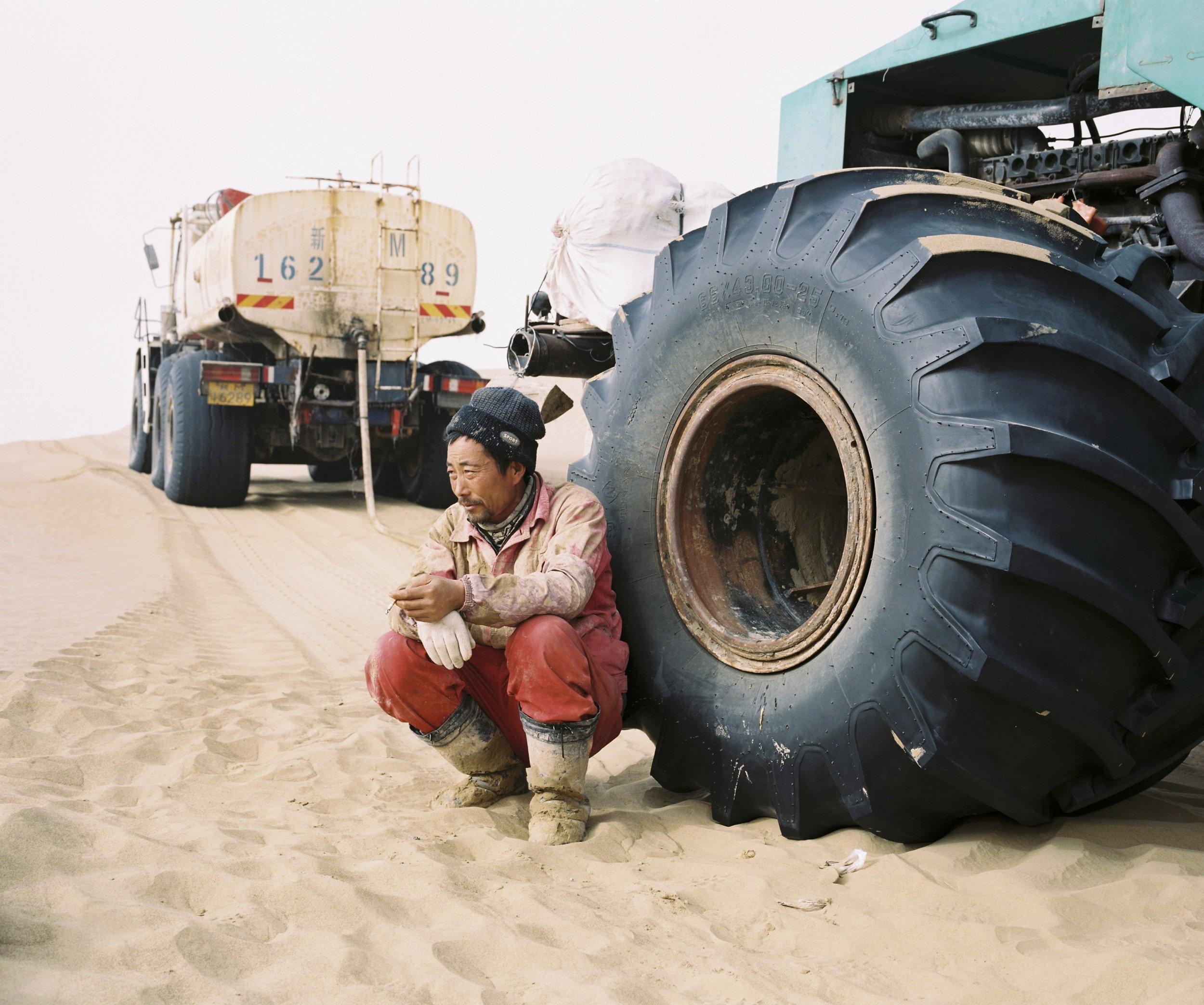 "December 2016. Xinjiang province, China. Senior technician from a Chinese state-owned oil company taking a cigarette break after lunch near one of the team's vehicle.  He is part of an oil exploration team from a Chinese state-owned company operating in the Taklamakan desert in the province of Xinjiang. This team and a few others are setting up thousands of explosive charges for weeks at a time that are all detonated at sthe same time to detect oil fields. Company is CNPC, China National Petroleum Corporation.  Xinjiang is the westernmost province in all China, located at the border of Central Asian countries, Russia and Mongolia. More than twice the size of France, it has only 22 million inhabitants, a majority of which are the indigenous Uighurs, a sunni-muslim Turkic ethnic group which has lived in the region for centuries. Tensions have nonetheless arisen in the last decade as a consequence of the en-masse migration of Han Chinese settlers and confessional persecution by the strongly secular governmental authorities.  Borrowing from romanticized notions of the American frontier, synonymous with ideals of exploration and expansion, photographer Patrick Wack captures a visual narrative of China's westernmost region—Xinjiang. Whereas the American West conjures images of cowboys and pioneers, of manifest destiny and individualistic freedom, the Chinese West has not yet been so defined. It is a place of pluralities—of haunting, expansive landscapes, of rough mountains and vivid lakes, of new construction and oil fields, of abandoned structures in decaying towns, of devout faith and calls to prayer, of silence and maligned minorities, of opportunity and uncertain futures. It is a land of shifting identity. In essence, Xinjiang is the new frontier to be conquered and pondered. Literally translating to ""new frontier"" in Chinese, Xinjiang is a land apart, and has been so for centuries. More than twice the land area of France with a population less than the city of Shanghai, the Chinese province of Xinjiang once connected China to Central Asia and Europe as the first leg of the ancient Silk Road. Yet it remains physically, culturally, and politically distinct, an otherness within modern China. Its infinite sense of space; its flowing Arabic scripts and mosque-filled cityscapes; its designation as an autonomous region; and simmering beneath, its uneasy relationship with the encroaching, imposing, surveilling East. For China's ethnic Han majority, Xinjiang is once again the new frontier, to be awakened for Beijing's new Silk Road—China's own manifest destiny—with the promise of prosperity in its plentiful oil fields. For Patrick Wack, Out West is as a much a story of the region as it is his own, as much a documentation of a contemporary and historical place as it is an emotional journey of what it means to strive, and for what. There exists an inherent fascination in the region—as both key and foil to the new China—and a siren's call to its vast limitlessness that instinctively incites introspection and desire. Showcasing a romanticism of the frontier, Out West presents Xinjiang via the lens of its present day, in photography that speaks of the surrealistic tranquility—and disquiet—of the unknown. Out West offers an experience of Xinjiang that highlights its estrangement from contemporary perceptions of the new China, accentuating undercurrents of tension and the mystique it has cultivated—whether in their minds or ours. At its core, Out West is a question of perspective: What is the West but the East to another?  Xinjiang is the westernmost province in all China, located at the border of Central Asian countries, Russia and Mongolia. More than twice the size of France, it has only 22 million inhabitants, a majority of which are the indigenous Uighurs, a sunni-muslim Turkic ethnic group which has lived in the region for centuries. Tensions have nonetheless arisen in the last decade as a consequence of the en-masse migration of Han Chinese settlers and confessional persecution by the strongly secular governmental authorities.  Borrowing from romanticized notions of the American frontier, synonymous with ideals of exploration and expansion, photographer Patrick Wack captures a visual narrative of China's westernmost region—Xinjiang. Whereas the American West conjures images of cowboys and pioneers, of manifest destiny and individualistic freedom, the Chinese West has not yet been so defined. It is a place of pluralities—of haunting, expansive landscapes, of rough mountains and vivid lakes, of new construction and oil fields, of abandoned structures in decaying towns, of devout faith and calls to prayer, of silence and maligned minorities, of opportunity and uncertain futures. It is a land of shifting identity. In essence, Xinjiang is the new frontier to be conquered and pondered. Literally translating to ""new frontier"" in Chinese, Xinjiang is a land apart, and has been so for centuries. More than twice the land area of France with a population less than the city of Shanghai, the Chinese province of Xinjiang once connected China to Central Asia and Europe as the first leg of the ancient Silk Road. Yet it remains physically, culturally, and politically distinct, an otherness within modern China. Its infinite sense of space; its flowing Arabic scripts and mosque-filled cityscapes; its designation as an autonomous region; and simmering beneath, its uneasy relationship with the encroaching, imposing, surveilling East. For China's ethnic Han majority, Xinjiang is once again the new frontier, to be awakened for Beijing's new Silk Road—China's own manifest destiny—with the promise of prosperity in its plentiful oil fields. For Patrick Wack, Out West is as a much a story of the region as it is his own, as much a documentation of a contemporary and historical place as it is an emotional journey of what it means to strive, and for what. There exists an inherent fascination in the region—as both key and foil to the new China—and a siren's call to its vast limitlessness that instinctively incites introspection and desire. Showcasing a romanticism of the frontier, Out West presents Xinjiang via the lens of its present day, in photography that speaks of the surrealistic tranquility—and disquiet—of the unknown. Out West offers an experience of Xinjiang that highlights its estrangement from contemporary perceptions of the new China, accentuating undercurrents of tension and the mystique it has cultivated—whether in their minds or ours. At its core, Out West is a question of perspective: What is the West but the East to another?"