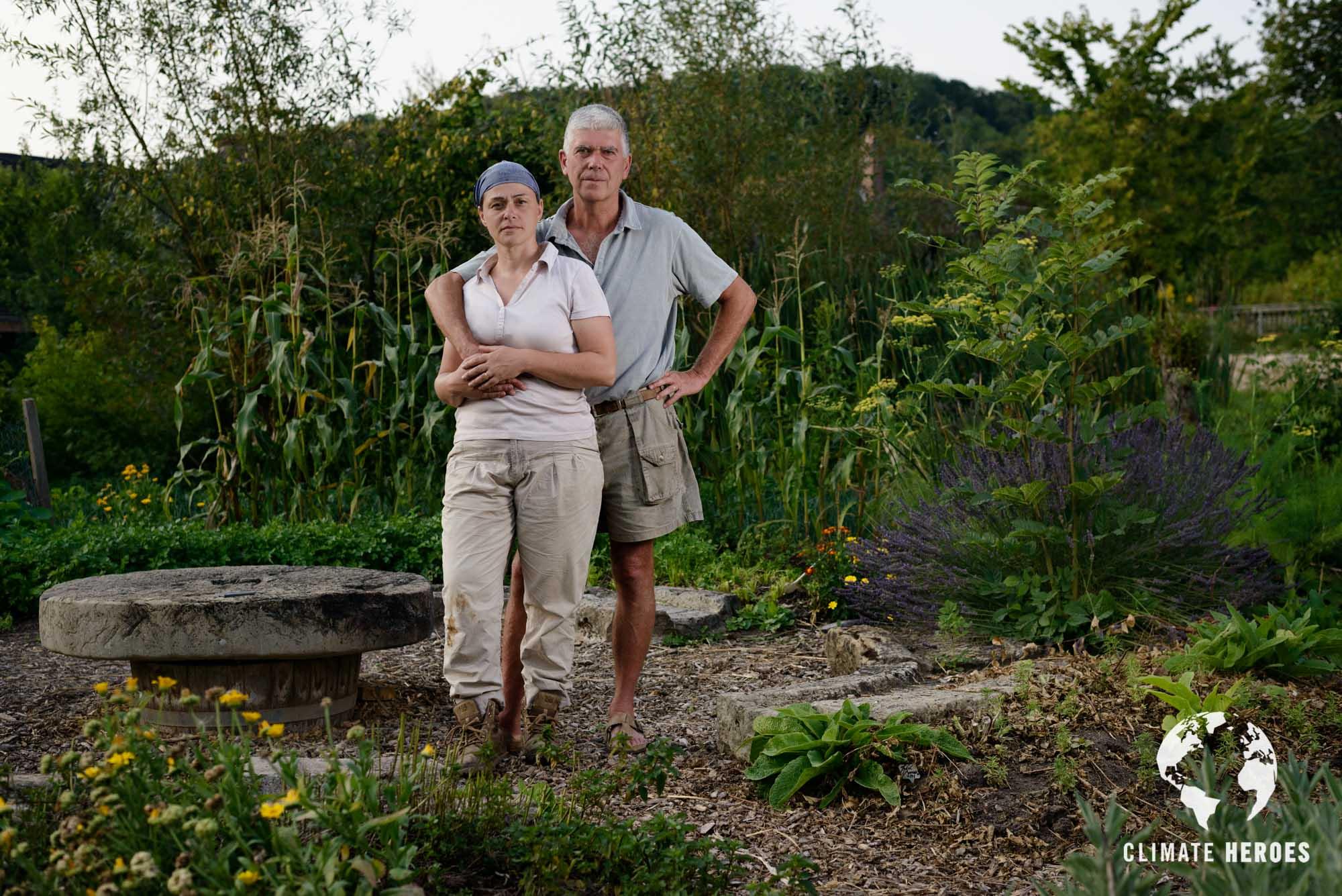 Portrait de Perrine et Charles Hervé Gruyer au centre du jardin de la Grande Ile, Ferme du Bec Hellouin. Leur maison se trouve à l'arrière plan.