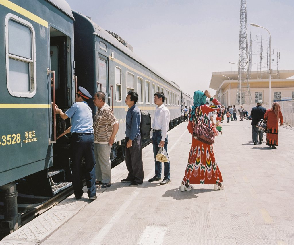 "May 2016. Xinjiang province, China. Travellers getting on and off the train to Hotan at the Kashgar railway station. This is the only railway linking the oasis towns south of the Taklamakan desert where most of Xinjiang's Uighur community in Xinjiang lives. Xinjiang is the westernmost province in all China, located at the border of Central Asian countries, Russia and Mongolia. More than twice the size of France, it has only 22 million inhabitants, a majority of which are the indigenous Uighurs, a sunni-muslim Turkic ethnic group which has lived in the region for centuries. Tensions have nonetheless arisen in the last decade as a consequence of the en-masse migration of Han Chinese settlers and confessional persecution by the strongly secular governmental authorities.  Borrowing from romanticized notions of the American frontier, synonymous with ideals of exploration and expansion, photographer Patrick Wack captures a visual narrative of China's westernmost region—Xinjiang. Whereas the American West conjures images of cowboys and pioneers, of manifest destiny and individualistic freedom, the Chinese West has not yet been so defined. It is a place of pluralities—of haunting, expansive landscapes, of rough mountains and vivid lakes, of new construction and oil fields, of abandoned structures in decaying towns, of devout faith and calls to prayer, of silence and maligned minorities, of opportunity and uncertain futures. It is a land of shifting identity. In essence, Xinjiang is the new frontier to be conquered and pondered. Literally translating to ""new frontier"" in Chinese, Xinjiang is a land apart, and has been so for centuries. More than twice the land area of France with a population less than the city of Shanghai, the Chinese province of Xinjiang once connected China to Central Asia and Europe as the first leg of the ancient Silk Road. Yet it remains physically, culturally, and politically distinct, an otherness within modern China. Its infinite sense of space; its flowing Arabic scripts and mosque-filled cityscapes; its designation as an autonomous region; and simmering beneath, its uneasy relationship with the encroaching, imposing, surveilling East. For China's ethnic Han majority, Xinjiang is once again the new frontier, to be awakened for Beijing's new Silk Road—China's own manifest destiny—with the promise of prosperity in its plentiful oil fields. For Patrick Wack, Out West is as a much a story of the region as it is his own, as much a documentation of a contemporary and historical place as it is an emotional journey of what it means to strive, and for what. There exists an inherent fascination in the region—as both key and foil to the new China—and a siren's call to its vast limitlessness that instinctively incites introspection and desire. Showcasing a romanticism of the frontier, Out West presents Xinjiang via the lens of its present day, in photography that speaks of the surrealistic tranquility—and disquiet—of the unknown. Out West offers an experience of Xinjiang that highlights its estrangement from contemporary perceptions of the new China, accentuating undercurrents of tension and the mystique it has cultivated—whether in their minds or ours. At its core, Out West is a question of perspective: What is the West but the East to another?"